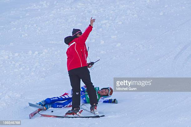 A course worker calls for a first aid team to assist Marie MarchandArvier of France after she crashed on the Kandahar course while competing in the...