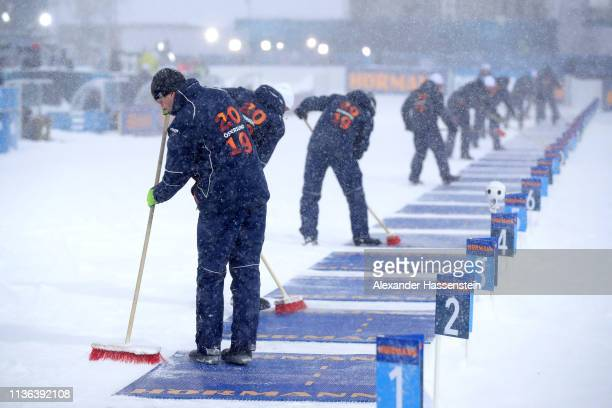 Course workers clean the shooting range during the Men's Mass Start at the IBU Biathlon World Championships on March 17 2019 in Ostersund Sweden