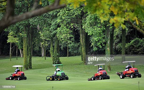 Course workers clear rain water along the fairway during day three of the Barclays Singapore Open Golf tournament at the Sentosa Golf Club in...