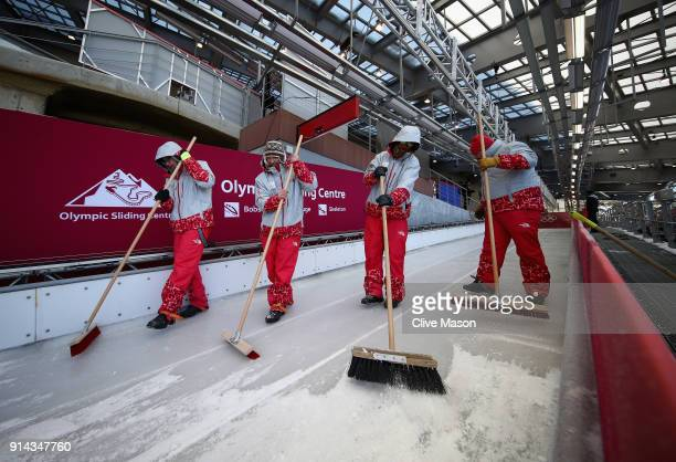 Course workers prepare the track during previews ahead of the PyeongChang 2018 Winter Olympic Games at the Alpensia Olympic Sliding Centre on...