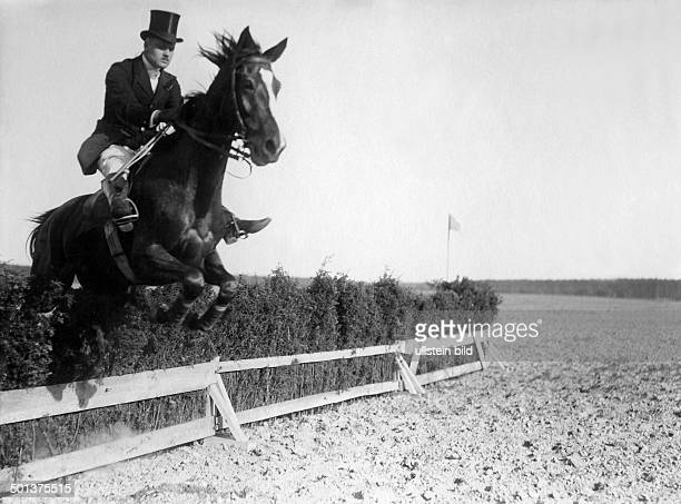 horseman and his horse jumping across an obstacle 1910
