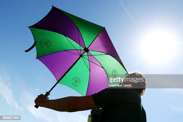 A court attendant holds an umbrella on day one of the Wimbledon Lawn Tennis Championships at All England Lawn Tennis and Croquet Club on July 2 2018...