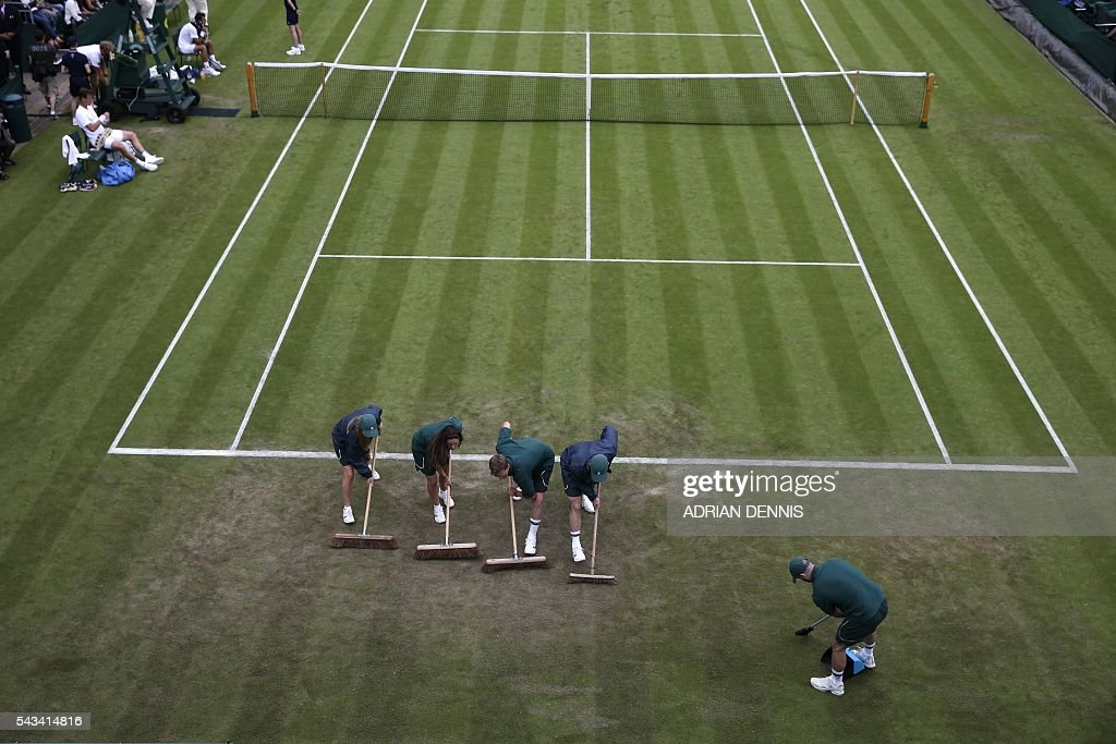TOPSHOT - Court attendants brush court 18 in a break between games between Croatia's Ivan Dodig and Czech Republic's Tomas Berdych during their men's singles first round match on the second day of the 2016 Wimbledon Championships at The All England Lawn Tennis Club in Wimbledon, southwest London, on June 28, 2016. / AFP / ADRIAN