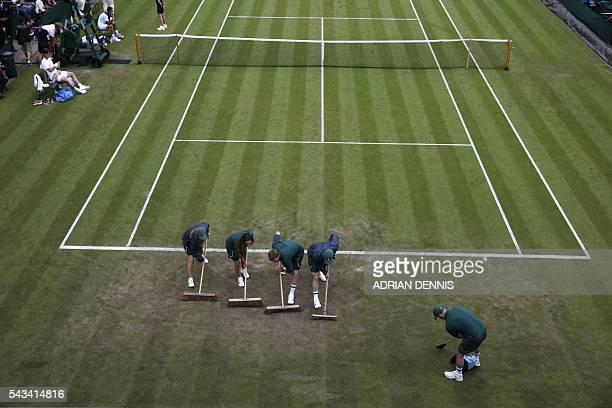 TOPSHOT Court attendants brush court 18 in a break between games between Croatia's Ivan Dodig and Czech Republic's Tomas Berdych during their men's...