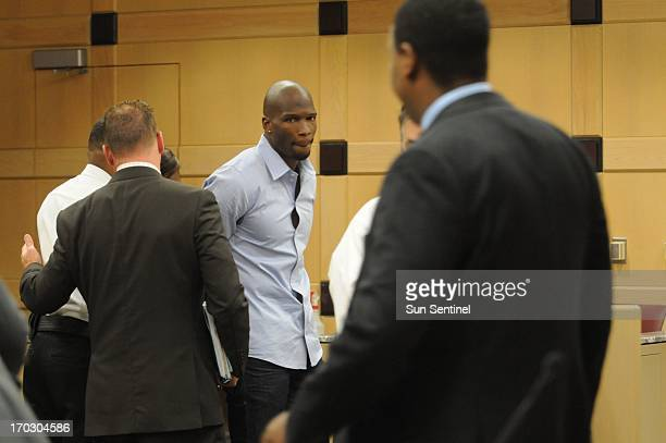 Court bailiffs hand cuff former Miami Dolphins wide receiver Chad Johnson after he was sentenced to 30 days in jail for a pat on his attorney's butt...
