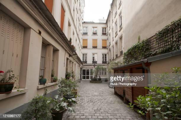 court between pre-war residential buildings in paris, france - courtyard - fotografias e filmes do acervo