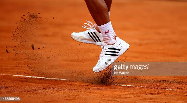 Court clay breaks up under Novak Djokovic of Serbia during his Men's Semi Final match against David Ferrer of Spain on Day Seven of The...