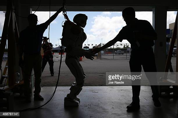 Court Edmondson and Phil Strawser work on the team NASA robot during the DARPA Robotics Challenge Trials at the HomesteadMiami Speedway on December...