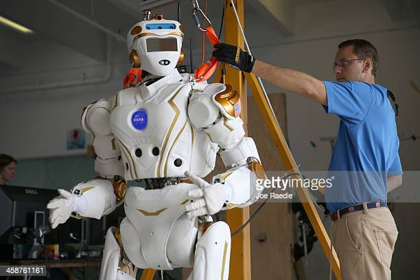 Court Edmondson works on the team NASA robot during the DARPA Robotics Challenge Trials at the HomesteadMiami Speedway on December 21 2013 in...