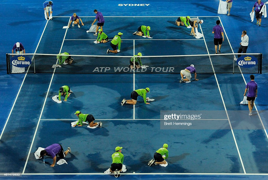 Court staff and ball kids work to dry the court ahead of the first round match between Nick Kyrgios of Australia and Jerzy Janowicz of Poland during day three of the Sydney International at Sydney Olympic Park Tennis Centre on January 13, 2015 in Sydney, Australia.