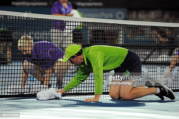 Court staff and ball kids work to dry the court ahead of the first round match between Nick Kyrgios of Australia and Jerzy Janowicz of Poland during...