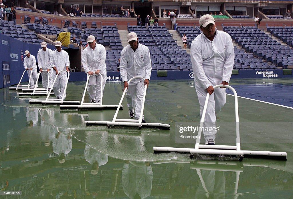 Court Technicians Squeegee The Tennis Court After Rainfall Inside