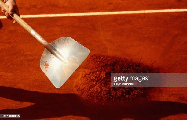 A court worker dresses the Manolo Santana court during day seven of the Mutua Madrid Open tennis tournament at the Caja Magica on May 11 2018 in...
