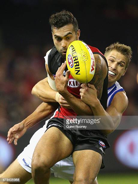 Courtenay Dempsey of the Bombers is tackled by Andrew Swallow of the Kangaroos during the round seven AFL match between the Essendon Bombers and the...