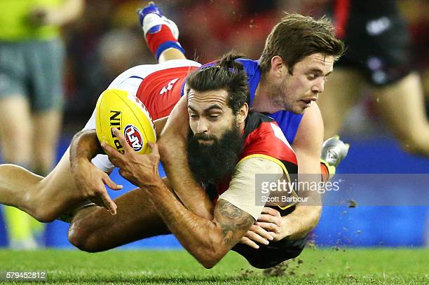 Courtenay Dempsey of the Bombers is tackled by Ryan Bastinac of the Lions during the round 18 AFL match between the Essendon Bombers and the Brisbane...