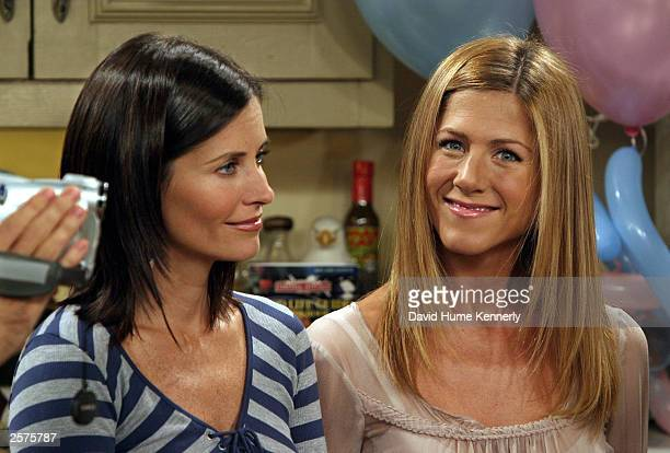 """Courteney Cox Arquette and Jennifer Aniston smile on the set of the hit NBC series """"Friends"""" during one of their last shows on the Warner Bros lot..."""