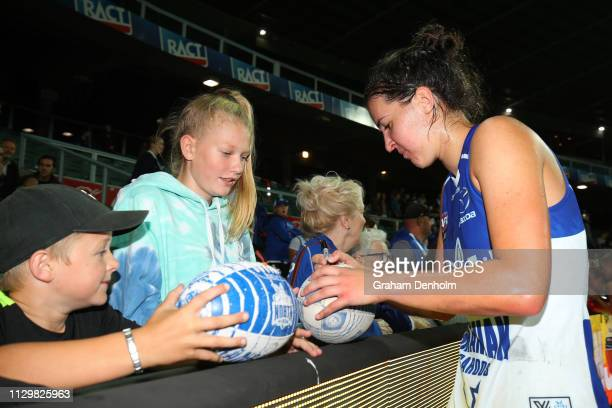 Courteney Munn of the Kangaroos signs her autograph for a young fan during the round three AFLW match between the North Melbourne Kangaroos and the...