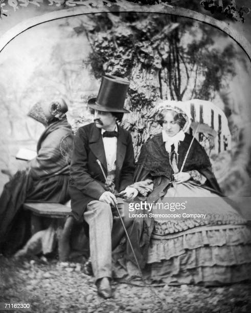 A courting couple in a London park hold hands while a chaperone sits beside them reading a book circa 1865