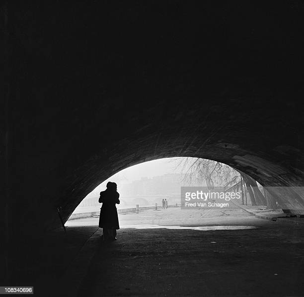Courting couple kissing under a bridge on the bank of the Seine, Paris, 1954.