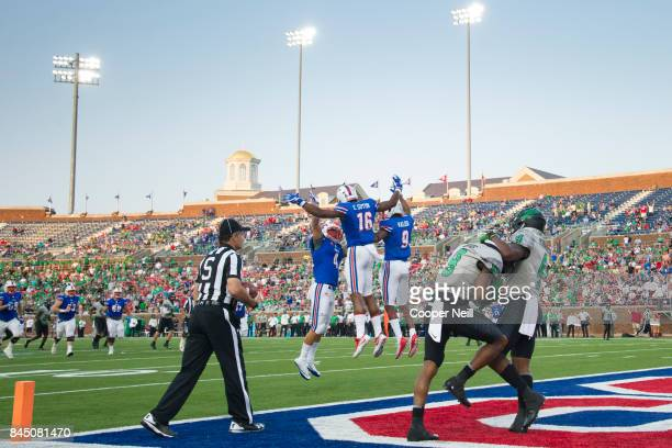 Courtland Sutton of the SMU Mustangs celebrates with teammates after scoring a touchdown against the North Texas Mean Green during the first half at...