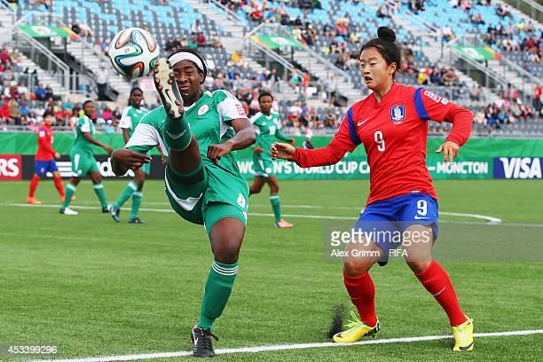 Courtney Dike of Nigeria is challenged by Choe Yuri of Korea Republic during the FIFA U20 Women's World Cup Canada 2014 group C match between Korea...