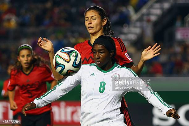 Courtney Dike of Nigeria is challenged by Paulina Solis of Mexico during the FIFA U20 Women's World Cup Canada 2014 group C match between Mexico and...