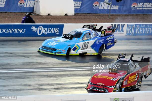 Courtney Force John Force Racing Chevrolet Camaro SS NHRA Funny Car slides sideways against Tim Wilkerson Ford Shelby Cobra Mustang NHRA Funny Car in...