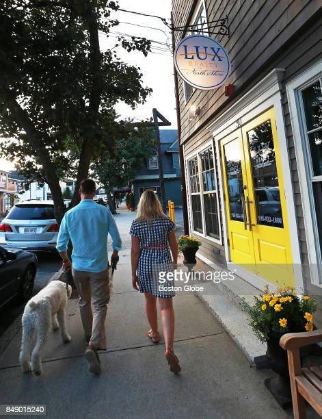 Courtney Hollands right and her husband Kevin Donovan pass a realtor's office while they walk around Beverly Farms in Beverly MA with their dog...