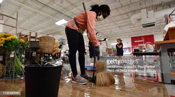 Courtney Igbo, of St. Paul, sweeps up debris at the T.J. Maxx store on University Avenue in St. Paul Friday, May 29, 2020. Hundreds of volunteers...