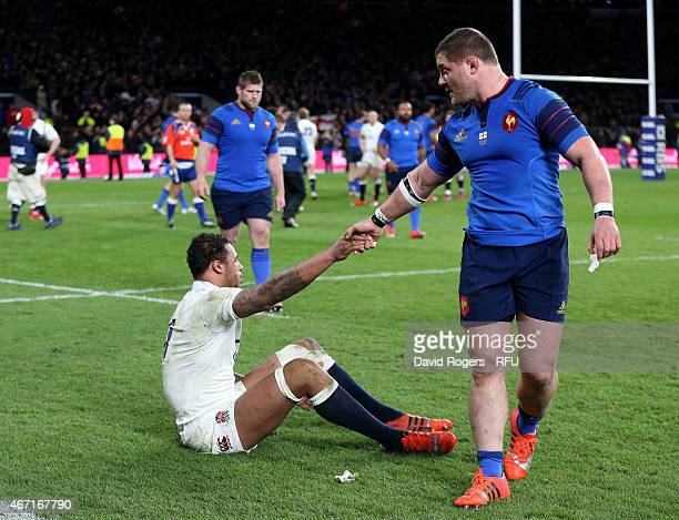 Courtney Lawes of England is helped up by Benjamin Kayser of France at the end of the RBS Six Nations match between England and France at Twickenham...