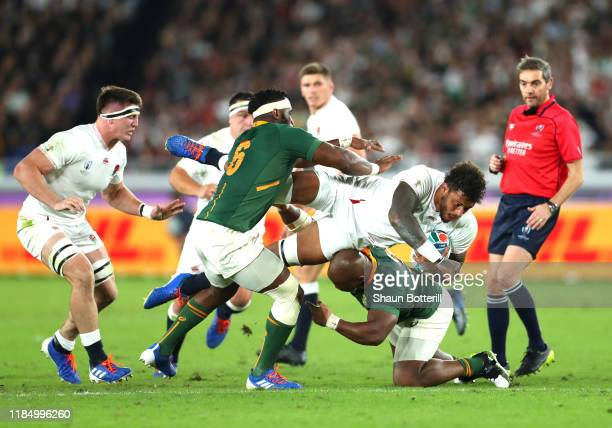 Courtney Lawes of England is tackled by Siya Kolisi and Mbongeni Mbonambi of South Africa during the Rugby World Cup 2019 Final between England and...