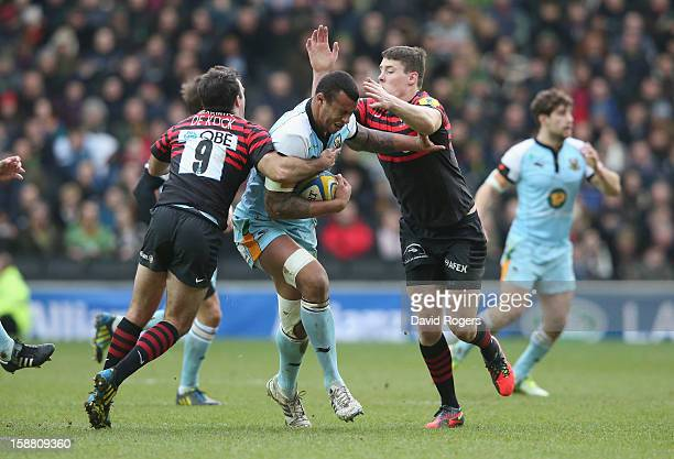 Courtney Lawes of Northampton is tackled by Neil de Kock and Joel Tomkins during the Aviva Premiership match between Saracens and Northampton Saints...