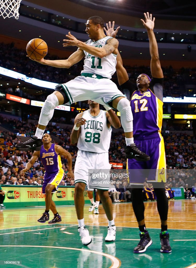 Courtney Lee #11 of the Boston Celtics goes midair underneath the basket for a pass in front of Dwight Howard #12 of the Los Angeles Lakers during the game on February 7, 2013 at TD Garden in Boston, Massachusetts.