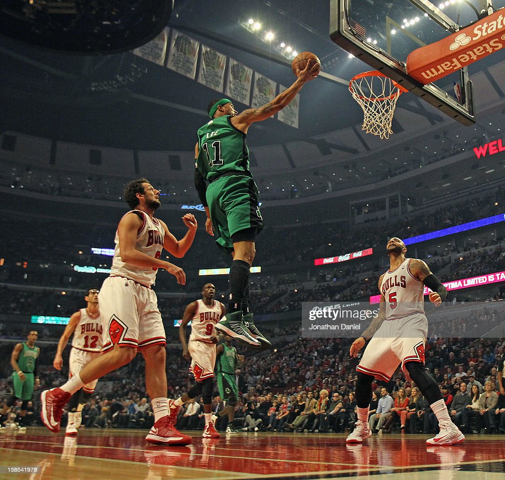 Courtney Lee #11 of the Boston Celtics goes up betrween Marco Belinelli #8 (L) and Carlos Boozer #5 of the Chicago Bulls at the United Center on December 18, 2012 in Chicago, Illinois.