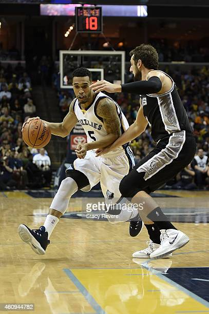 Courtney Lee of the Memphis Grizzlies drives around Marco Belinelli of the San Antonio Spurs during a game at the FedExForum on December 30 2014 in...