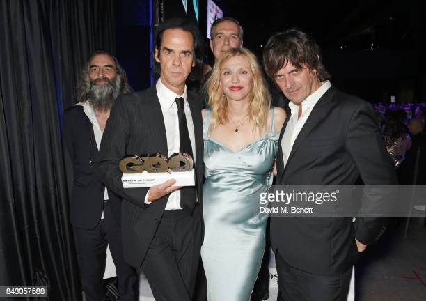 Courtney Love poses with Nick Cave The Bad Seeds winners of the Band of the Year award at the GQ Men Of The Year Awards at the Tate Modern on...