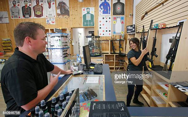 Courtney Manwaring shows an AR15 semiautomatic gun to David Barker at Action Target on June 17 2016 in Springville Utah Semiautomatics are in the...