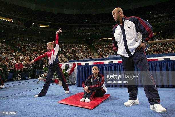 Courtney McCool stretches as Terin Humphrey and coach Al Fong watch during the Women's preliminaries of the US Gymnastics Olympic Team Trials on June...