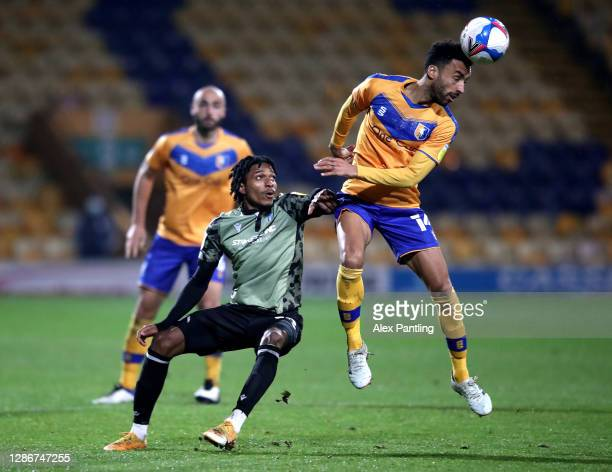 Courtney Senior of Colchester tackles James Perch of Mansfield during the Sky Bet League Two match between Mansfield Town and Colchester United at...