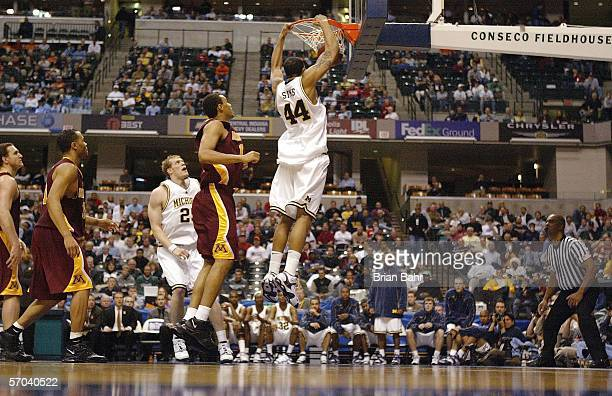 Courtney Sims of the Michigan Wolverines dunks the ball against the Minnesota Golden Gophers during Day 1 of the Big 10 Tournament on March 9 2006 at...