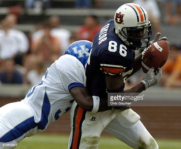 Courtney Taylor of the Auburn Tigers is tackled by Antoine Huffman of Kentucky Wildcats after making a first down catch on October 23 2004 at...