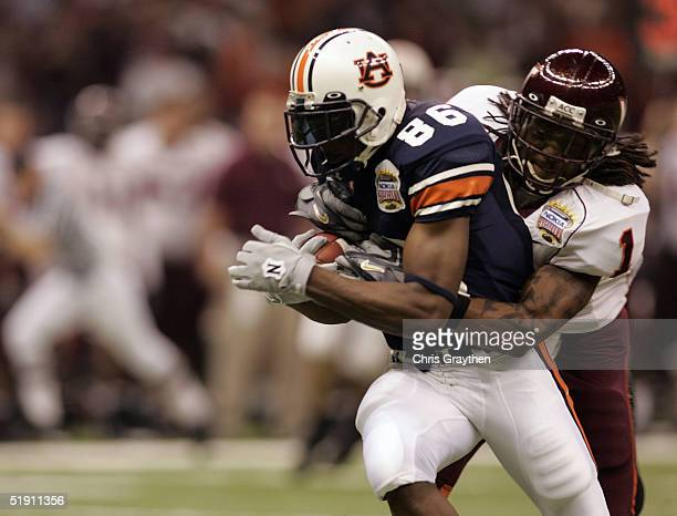 Courtney Taylor of the Auburn Tigers is tackled by Eric Green of the Virginia Tech Hokies during the Nokia Sugar Bowl on January 3, 2005 at the...
