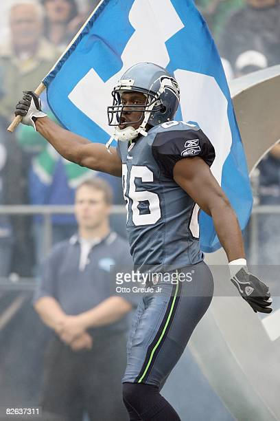 Courtney Taylor of the Seattle Seahawks carries the 12th man flag as he enters the field the game against the Oakland Raiders at Qwest Field on...