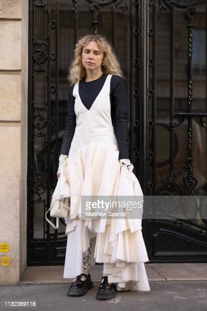 Courtney Trop is seen on the street during Paris Fashion Week AW19 wearing white dress with black shirt and Marine Serre undershirt and leggings on...