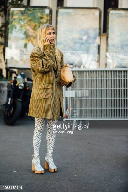 Courtney Trop talks on the phone and wears a yellow check oversized blazer tan Margiela bag Marine Serre print tights and silver heels during Paris...