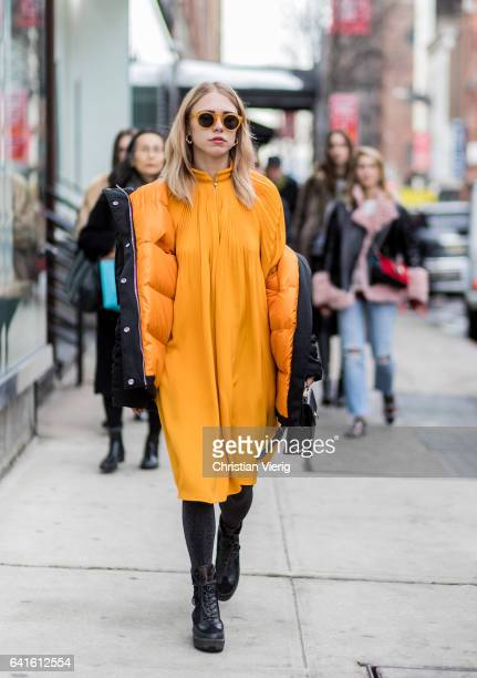 Courtney Trop wearing a yellow dress black down feather jacket outside Tibi on February 11 2017 in New York City