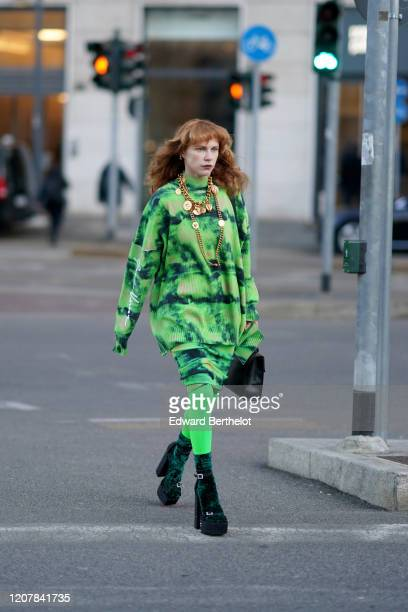 Courtney Trop wears golden necklaces, a green oversized pullover with long sleeves, green leggings, a bag, platform shoes, outside Versace, during...