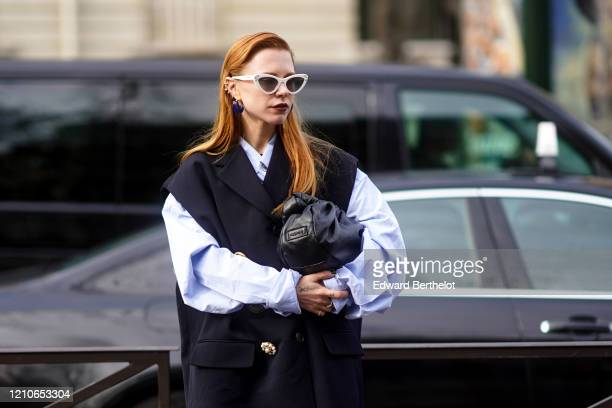 Courtney Trop wears sunglasses, a black leather puff bag, a shirt, a sleeveless oversized jacket, outside Miu Miu, during Paris Fashion Week -...
