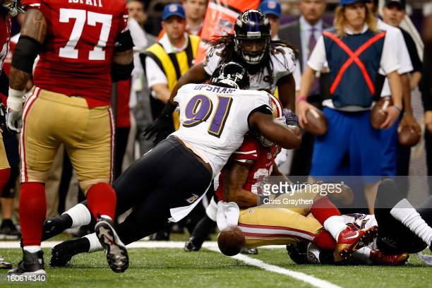 Courtney Upshaw of the Baltimore Ravens forces a fumble from LaMichael James of the San Francisco 49ers in the second quarter during Super Bowl XLVII...