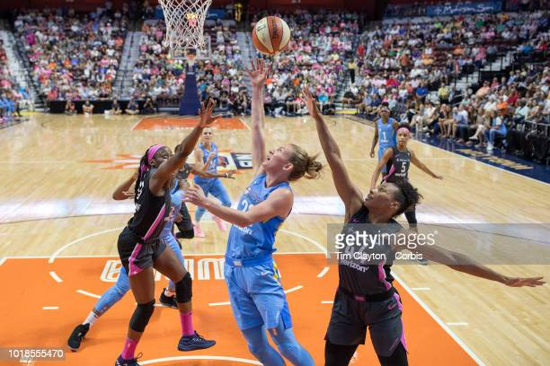 Courtney Vandersloot of the Chicago Sky drives to the basket defended by Betnijah Laney of the Connecticut Sun and Chiney Ogwumike of the Connecticut...